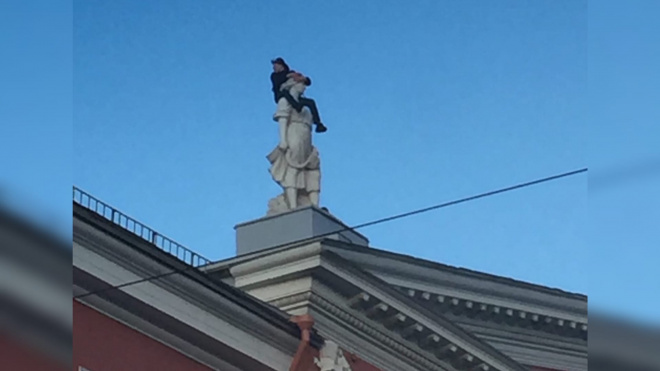 Петербуржец залез на голову статуи на крыше дома Невского проспекта