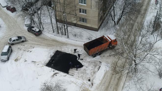 На севере Петербурга рабочие кладут асфальт поверх снега