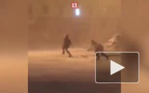 Сильный ветер в Норильске заставляет людей ползти по улице